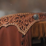 Tooled and dyed yokes with buckstitch detail.  Silver overly concho at back sides.
