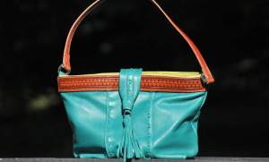 Turquoise over the shoulder purse lined with a pocket.
